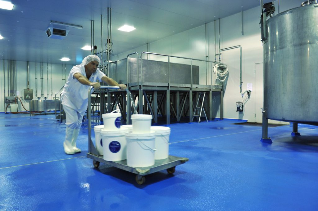 Worker pushing trolley on blue epoxy floor